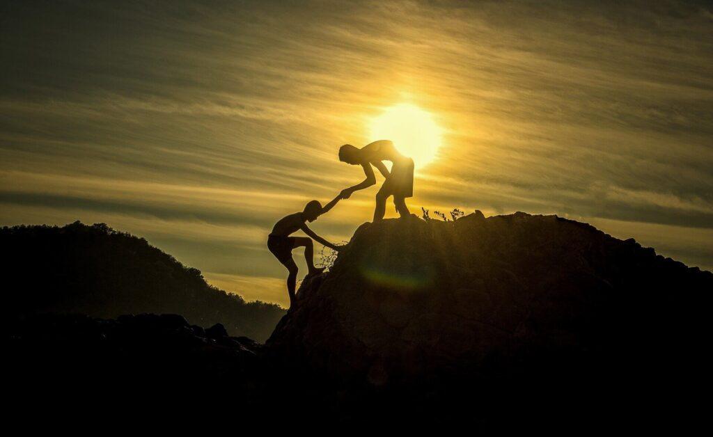 協力して山を登っている人たち